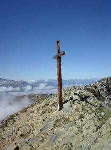 Croix planter en haut d'une montagne, en fond la vallée et des nuages