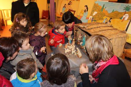 enfant admirant le creche lors de la célébration de la paroisse ste anne de lizeron