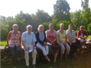 l'équipe pastorale de la paroisse sainte anne de lizeron pose sur un mur, photo de groupe